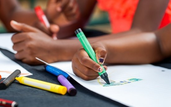 Mãos de crianças negras com giz de cera desenhando em um papel