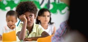 Estudante sentado em sala de aula com expressão de descontentamento e agitação segura um lápis azul e olha para frente