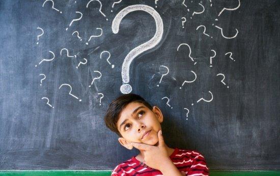 Estudante em dúvida na frente de uma lousa com pontos de interrogação desenhados