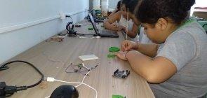 3 alunos de cerca de 9 anos trabalhando com materiais como palitos e eletrônicos em uma bancada de madeira encostada na parede