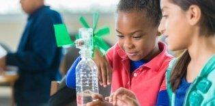 Duas meninas de cerca de 8 anos construindo um cata vento com garrafas plásticas
