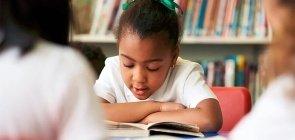 Menina lê livro na biblioteca da escola