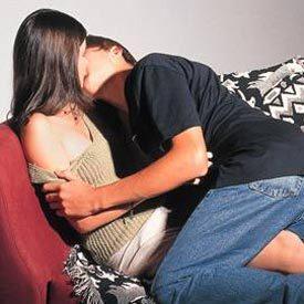 Jovens se beijando no sofá: idade de amadurecimento e riscos de gravidez. Foto: Marcio Capovilla