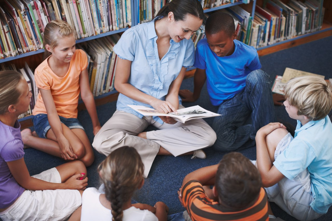 Professora sentada no chão com as pernas cruzadas rodeada por alunos em uma biblioteca