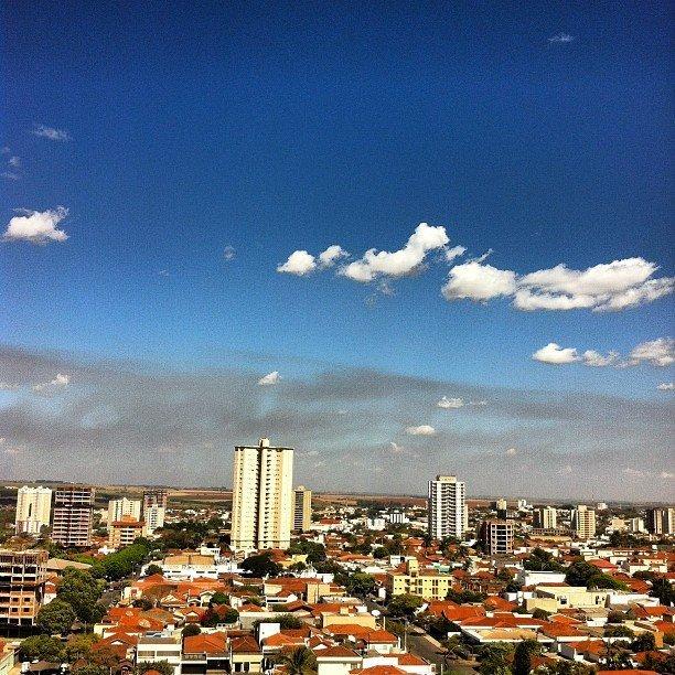 Céu azul com uma nuvem. Cidade com maioria de casas e apenas um prédio de altura mediana no centro da imagem