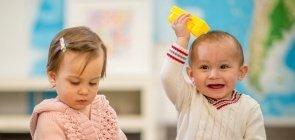 Crianças pequenas brincam com peças de montar na sala de aula da creche