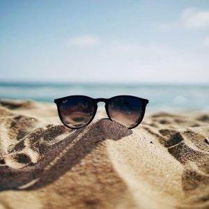 Um óculos de sol apoiado na areia. No fundo, vê-se o horizonte do mar
