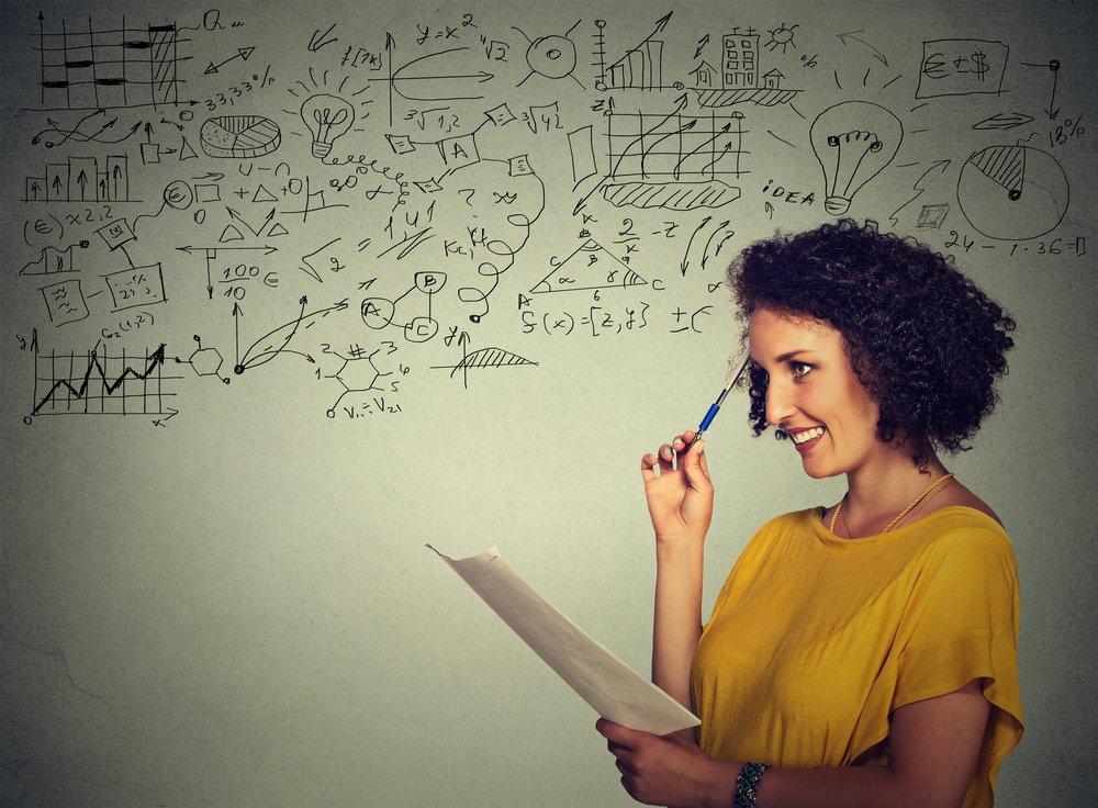 Mulher de cabelos cacheados de lado segurando papel e encostando a ponta de uma caneta na cabeça com a outra mão