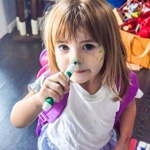 Menina com rosto pintado por canetinha