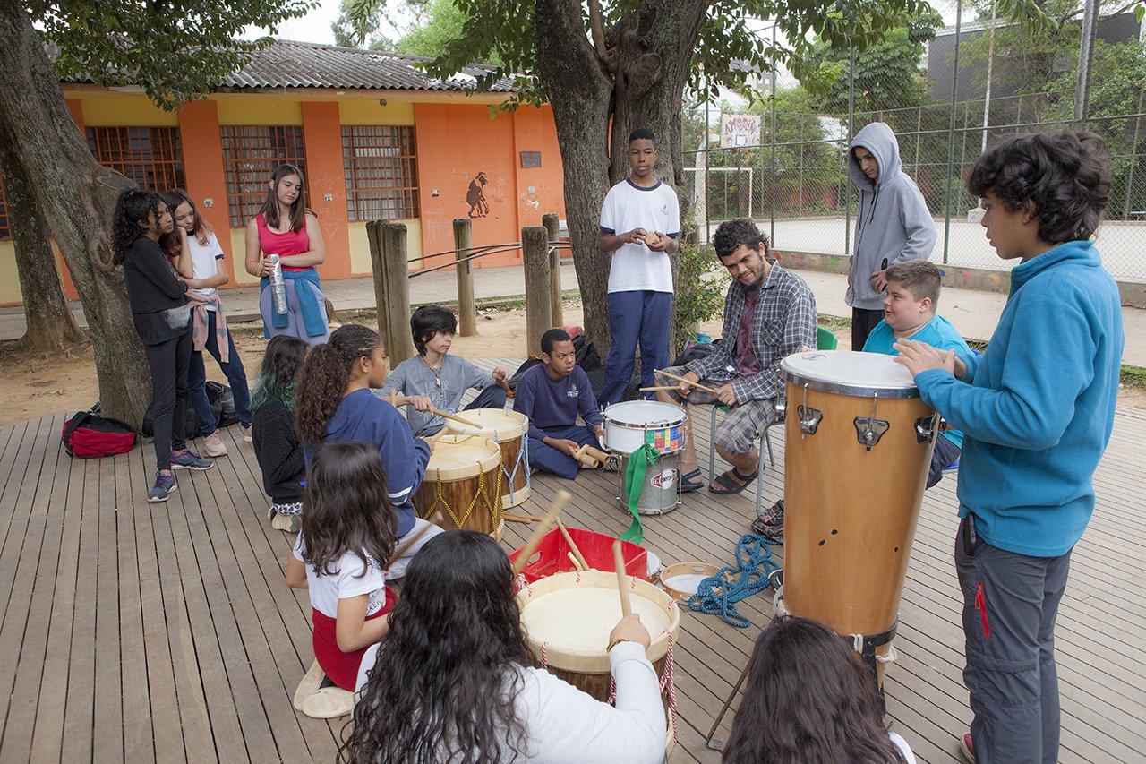 Alunos da escola municipal Desembargador Amorim Lima tocam instrumentos na área externa com muros coloridos
