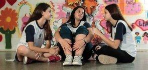 Com um fundo grafitado, três meninas vestem uniforme e conversam sentadas no chão