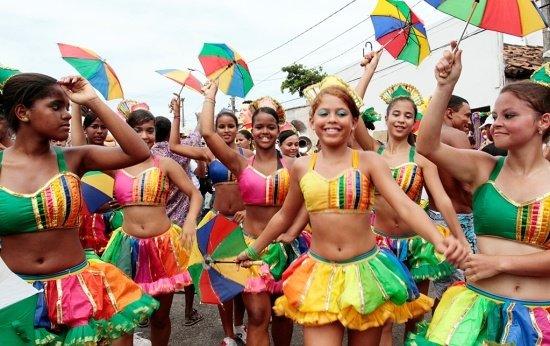 Meninas em pé com sombrinhas de Frevo e roupas coloridas