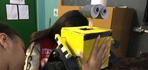 Uma aluna de cerca de 14 anos atrás de um robo da animação wall-e