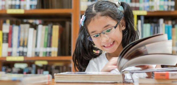 Criança de cerca de 7 anos lê livro em cima de uma. Ela sorri (Crédito: Shutterstock)