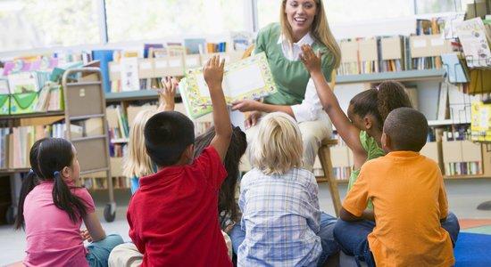 Professora sentada em um banco alto mostra livro para alunos sentados no chão