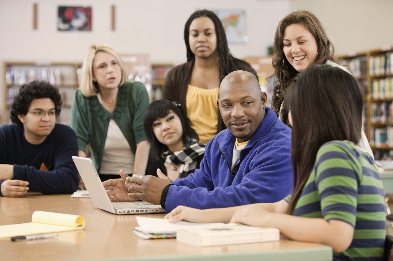 Professor sentado em uma mesa longa em uma sala de aula está cercado por outros alunos mais velhos