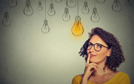 Mulher pensativa diante de várias lâmpadas desenhadas na parede, apagadas, e uma acesa