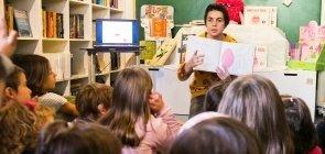 A autora Olga de Dios lendo seus livros para um grupo de crianças