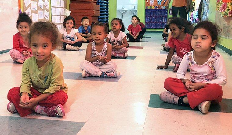 Crianças sentadas no chão de uma creche de São Paulo praticam em ioga