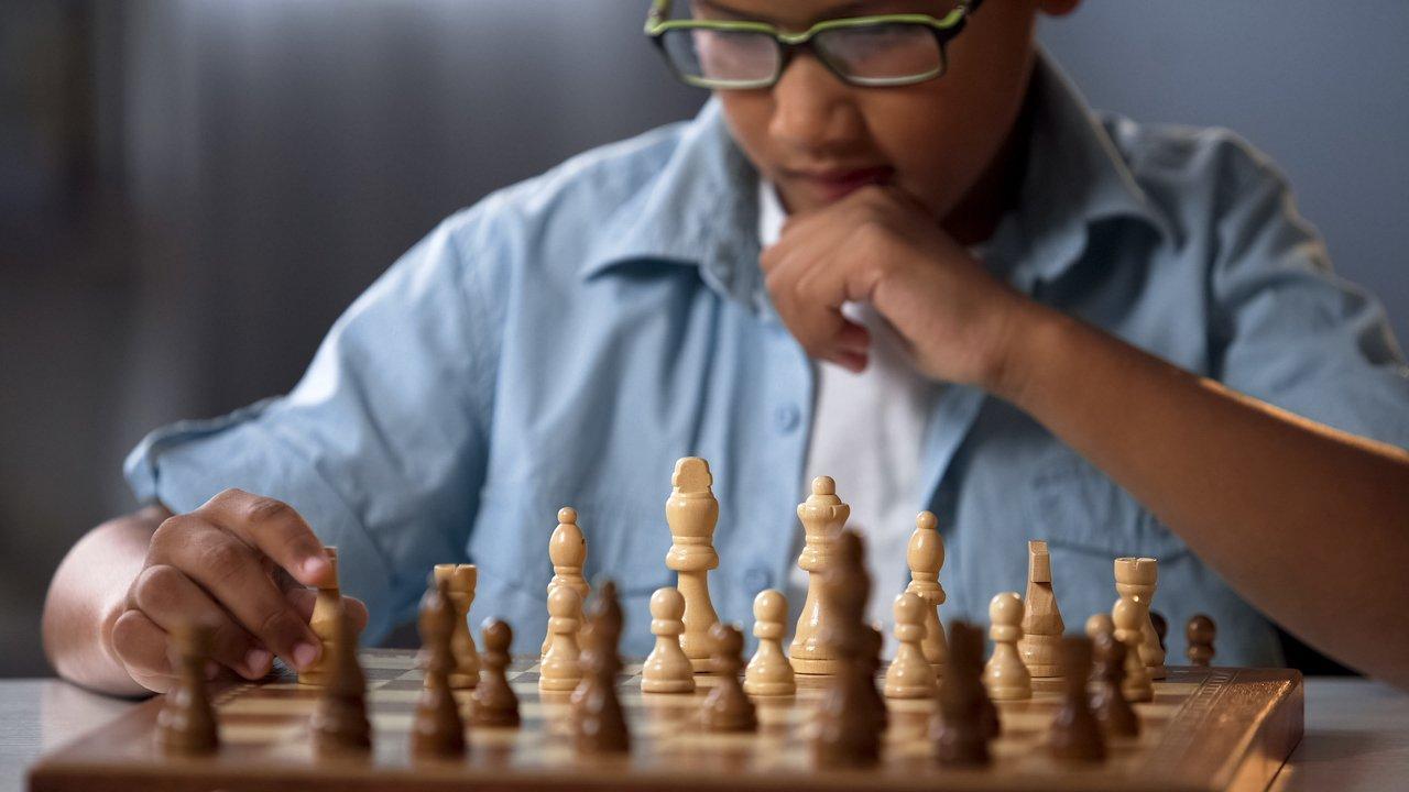 Estudante pensa diante de um tabuleiro de xadrez