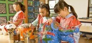 Meninas pintam objeto de papel marchê em ateliê de artes