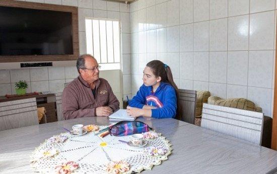 Dentro de uma cozinha ampla, uma menina de cerca de 15 anos e seu avó estão sentados se olhando. A menina segura o lápis para anotar as histórias que ele conta.