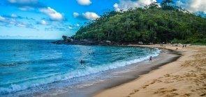 Praia com pedras e mata atlântica ao fundo