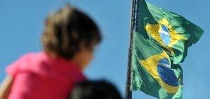 Menino assiste nos ombros do pai o hasteamento da bandeira do Brasil durante comemorações do Dia da Bandeira em Brasília