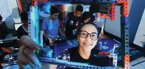 Aluna em aula de robótica segura peça construida na aula de robótica. Ela usa óculos, sorri e está com o cabelo preso
