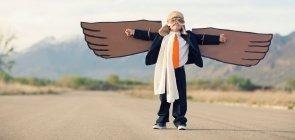 Um menino de cerca de 6 anos em uma estrada. Ele está vestindo um capacete e asas de papelão