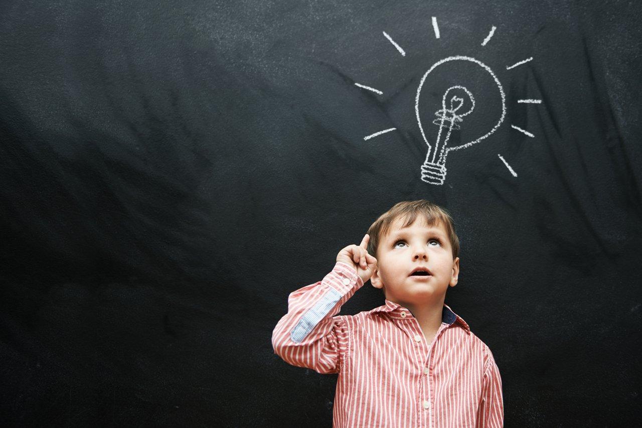 menino em frente a uma lousa com o desenho de uma lâmpada