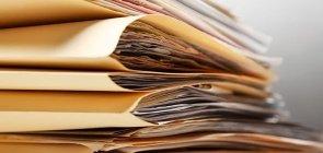 Documentos organizados dentro de pastas e empilhados