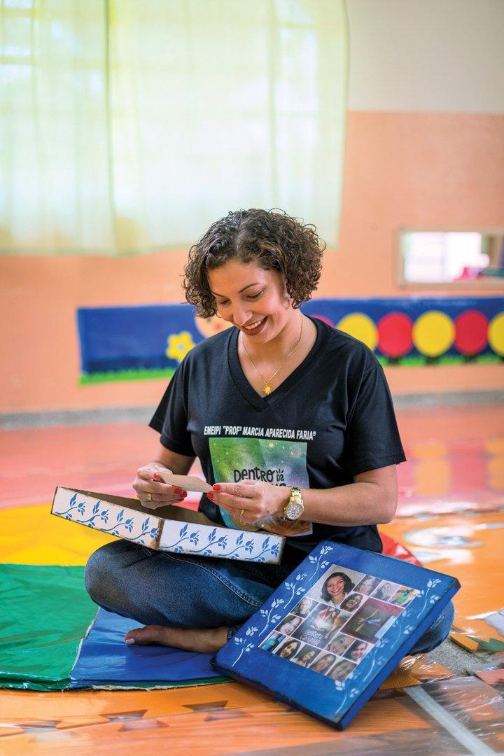 Coordenadora Pedagógica Karina, sentada de pernas cruzadas, lança um olhar carinhoso para uma das fotos de sua infância que trouxe para compartilhar com os professores.