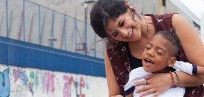 A professora Débora Carvalho, da EMEI Profa. Luciana Azevedo Pompermayer, em São Paulo, dá atenção a Kaynã, menino com deficiências múltiplas, e o leva para brincar com os colegas no pátio da unidade escolar