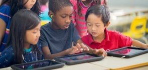 Grupo de alunos reunidos em torno de uma mesa em uma sala de aula brinca com tablets