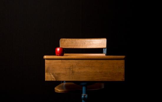 Mesa e cadeira de estudante em madeira, sobre fundo preto, com uma maçã vermelha