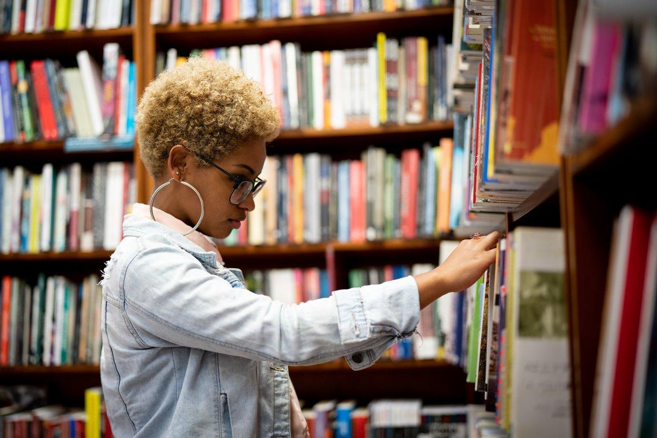Aluna retira livro de estante em meio às prateleiras de uma biblioteca