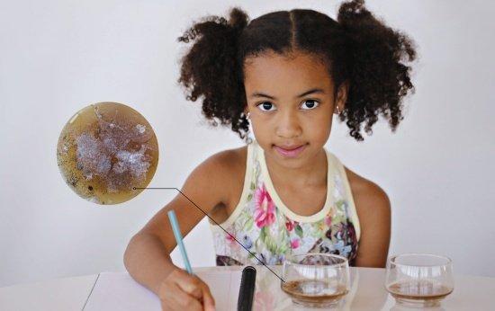 Garota fazendo anotações sobre experimento científico