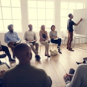 Professores em roda em uma sala olham para outro professor que escreve numa lousa