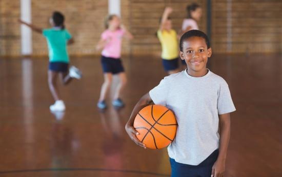 Menino usando camiseta branca segurando uma bola de basquete. Seus colegas jogam ao fundo.