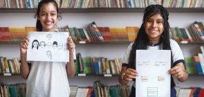Duas alunas mostrando desenhos das árvores genealógicas das suas famílias
