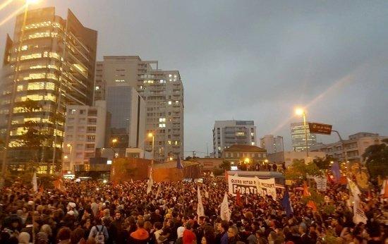 Centenas de manifestantes reunidos com faixas e cartazes