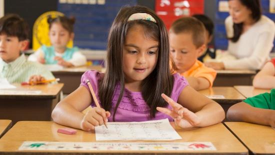 Menina sentada diante da mesa com lápis e papel fazendo contas com os dedos