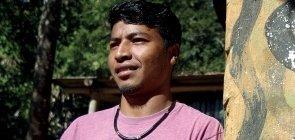 Homem indígena está usando camiseta rosa, ele olha para o lado e está com os braços cruzados