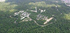 Vista aérea do campus da UFAM, onde se pode ver alguns prédios em meio a uma vasta área de floresta