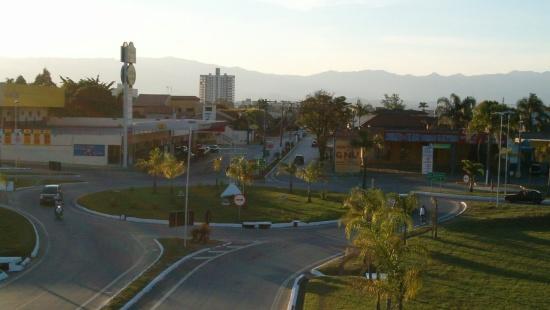 rotatória da entrada da cidade de Lorena com uma grande área verde ao centro e lojas na beira da avenida