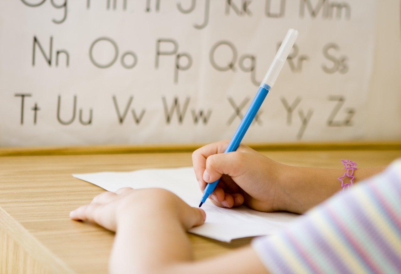 Braço de criança aparece escrevendo em cima de uma mesa com o alfabeto ao fundo