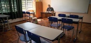 Professor senta sozinho em uma sala de aula, ele aparece no fundo lendo sentado, usa camiseta preta e óculos