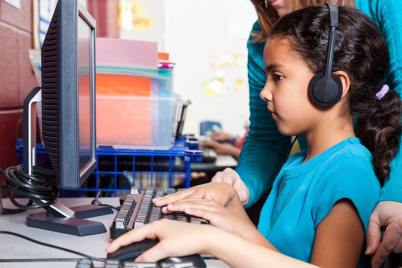 Aluna usa o computador com ajuda da professora em uma sala de aula