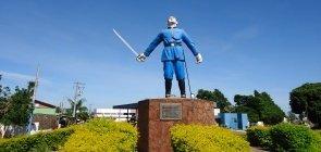 estátua de um homem com espada e vestindo uniforme azul no meio de uma praça aberta